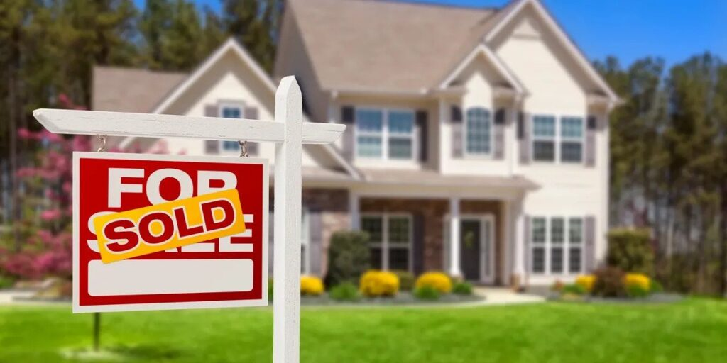 Live focus picture of a sold sign with a beautiful two-story suburban house in the background.